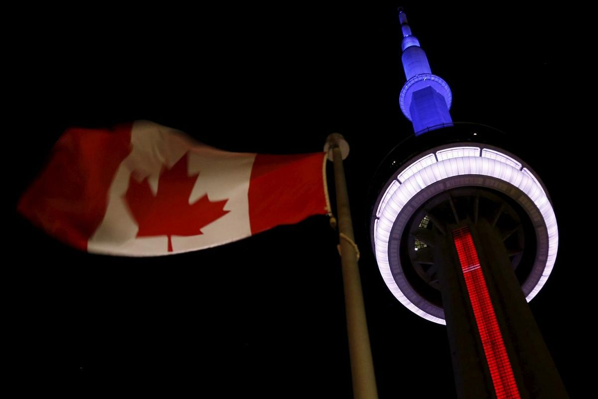 The landmark CN Tower is lit in the colors of the French flag in Toronto, Canada.
