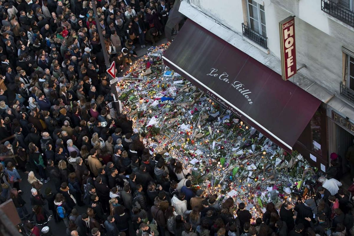 A large crowd gathers to lay flowers and candles in front of the Carillon restaurant in Paris on Nov 15, 2015.