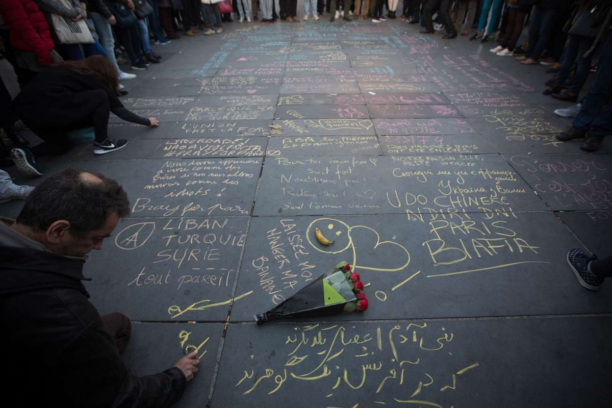 Mourners writing messages in chalk at Place de la Republique after the terrorist attacks in Paris, on Sunday, Nov 15, 2015.