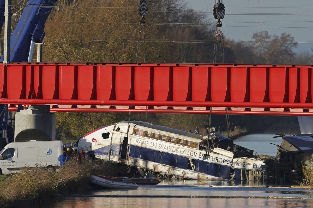 Workers using cranes to lift a carriage of a test TGV train that derailed and crashed, killing at least 10 people on Saturday, in a canal outside Eckwersheim near Strasbourg in eastern France on Nov 15, 2015.