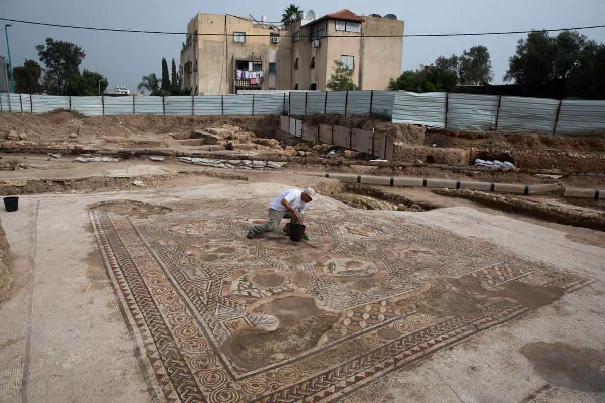 A worker of the Israel Antiquities Authority cleans a 1,700-year-old mosaic, which served as pavement for the courtyard in a villa during the Roman and Byzantine periods, Nov 16, 2015.