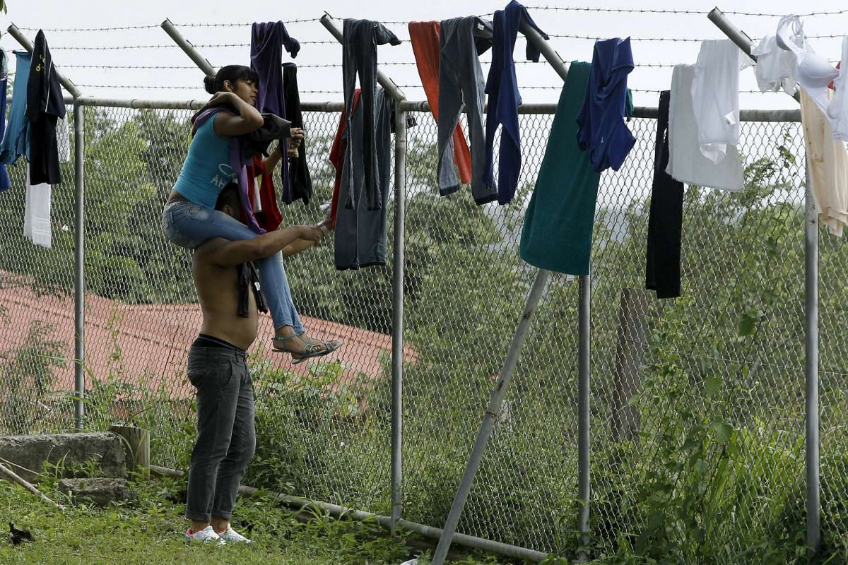 Cuban migrants dry their clothes at a temporary shelters in a school in the town of La Cruz, near the border between Costa Rica and Nicaragua, Nov 16, 2015.