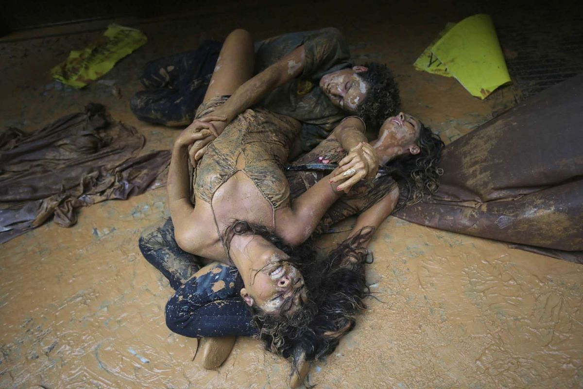 Protesters perform lying in muddy water which they splashed at the entrance to Vale headquarters in Rio de Janeiro, Brazil, in protests against the two Samarco dams that burst and led to severe environmental damage.