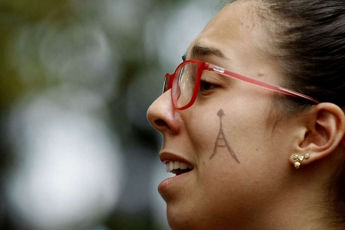 A woman participates with French residents in a minute of silence in Medellin, Colombia, in light of Friday's Paris attacks, on Nov 16, 2015.