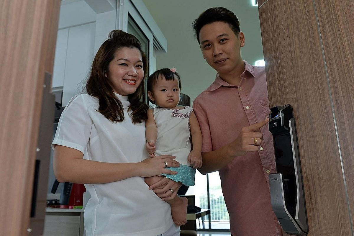 Mr Andy Wee,33, showing the Samsung digital lock he had installed at his Yishun DBSS apartment. With him are his wife, Apel, 28, and their 16-month-old daughter Charlize.