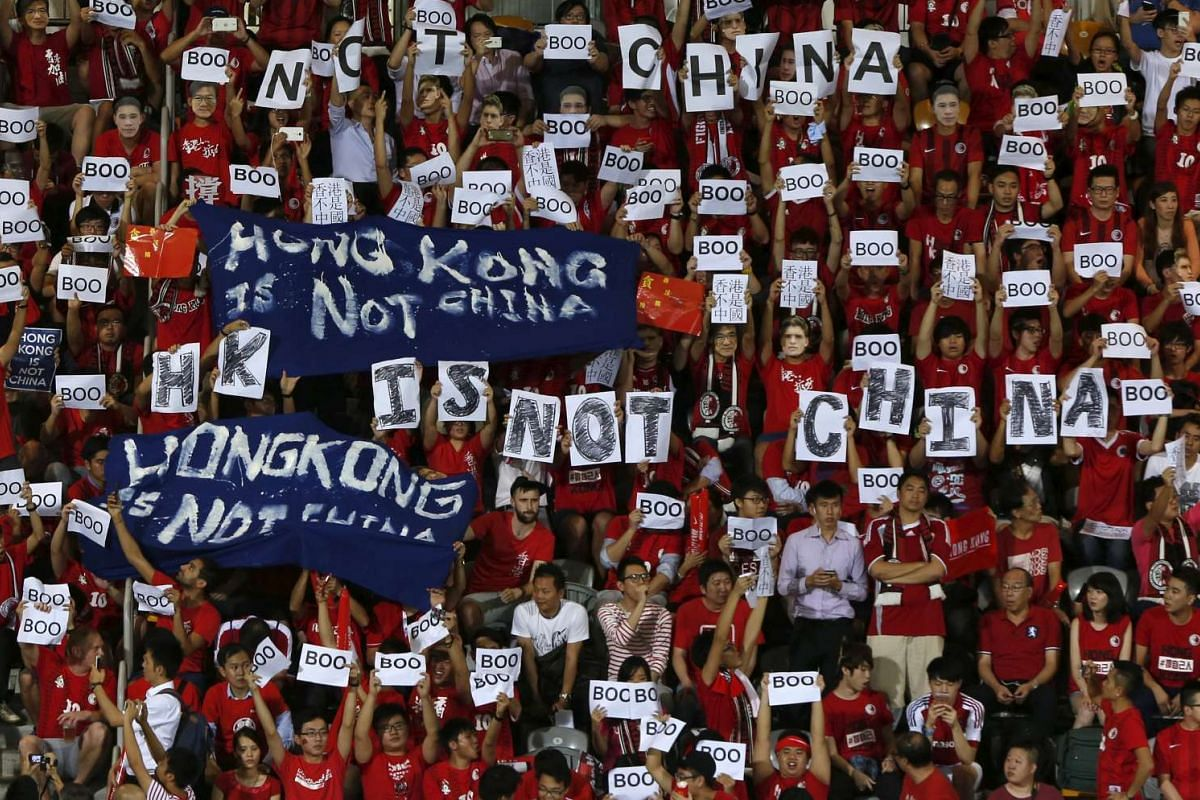 """Hong Kong fans hold banners and character signs which read """"Hong Kong is not China"""", during the Chinese national anthem at the 2018 World Cup qualifying match between Hong Kong and China, in Hong Kong, China November 17, 2015.  PHOTO: REUTERS"""