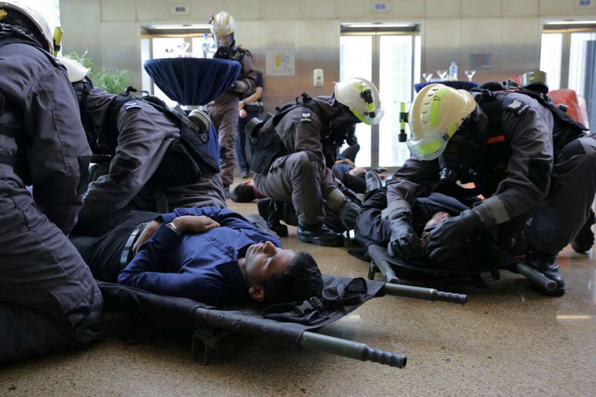 SCDF front-line firefighters attending to victims at One Marina Boulevard during one of the scenarios simulating a chemical agent attack.