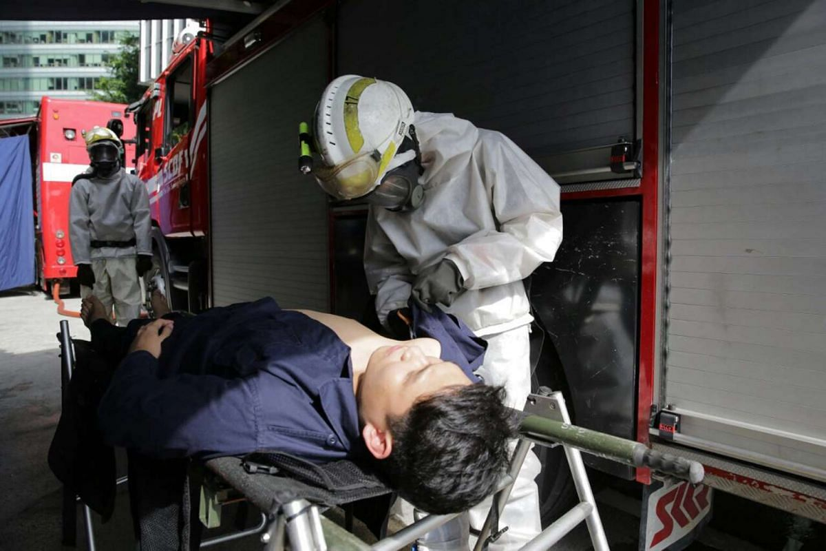 An SCDF personnel cutting open a victim's clothes for the decontamination process after a chemical agent attack.