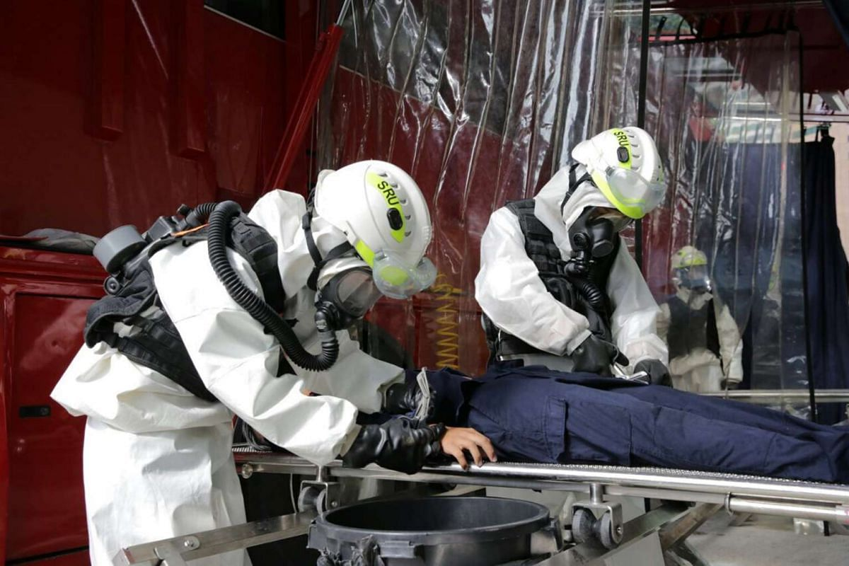 SCDF personnel cutting open a victim's clothes for the decontamination process after a chemical agent attack.
