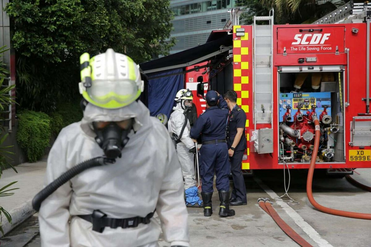 SCDF personnel standing near a fire engine after a chemical agent attack.