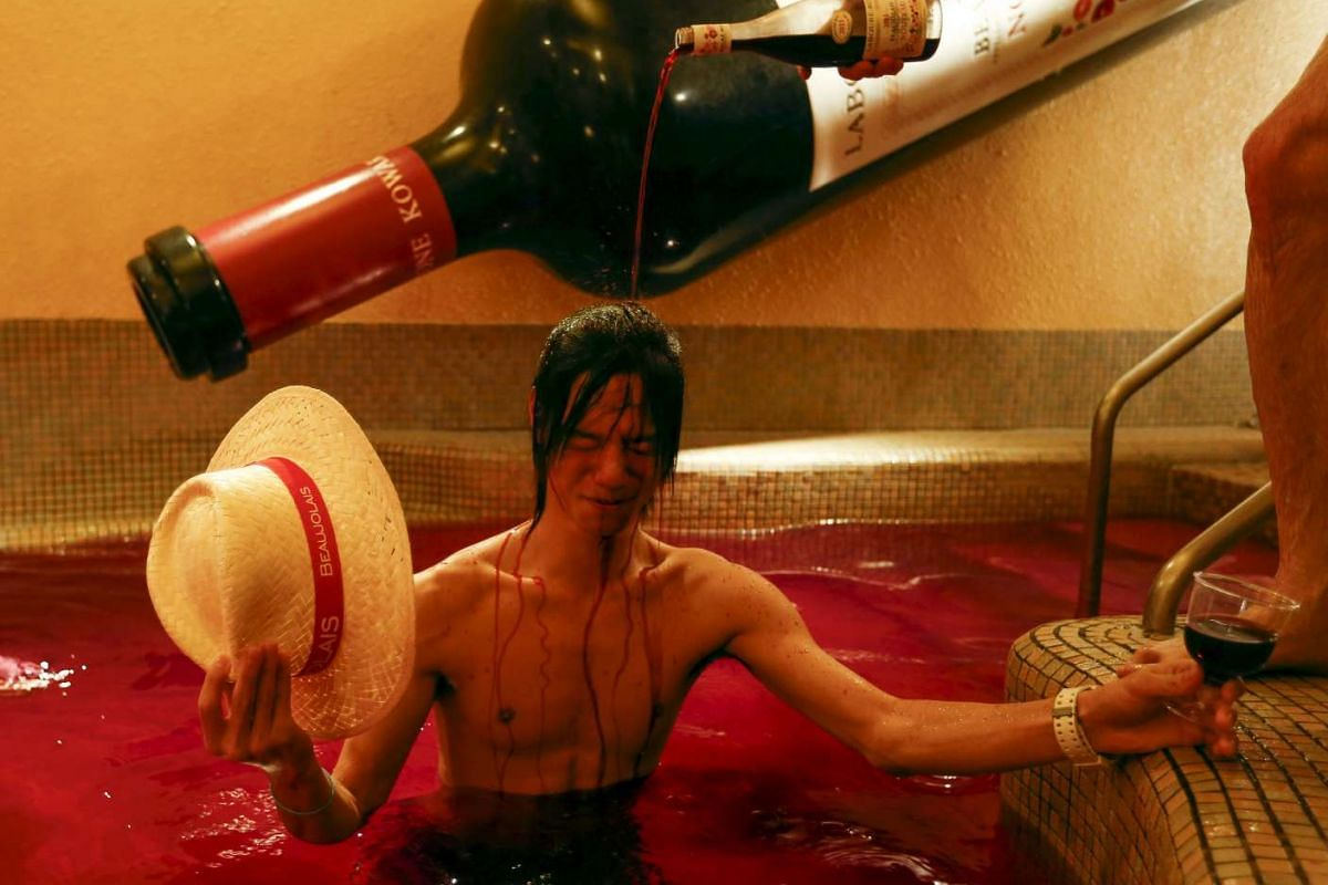A man pouring wine over a customer in a hot bath of coloured water representing wine at the Hakone Kowaki-en Yunessun spa resort to mark Beaujolais Nouveau Day in Hakone, west of Tokyo, on Nov 19, 2015. PHOTO: REUTERS