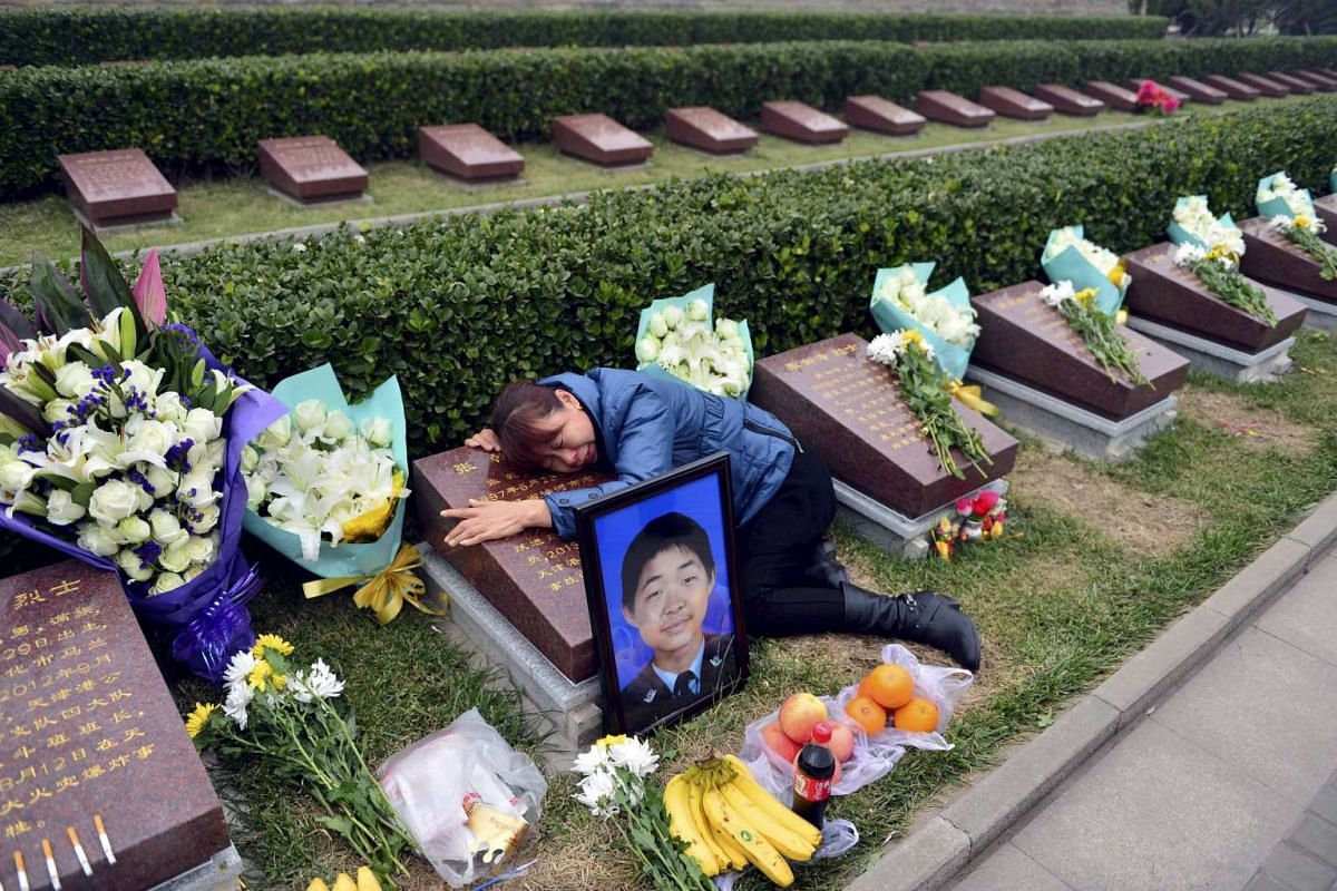 The mother of a young policeman killed during the Tianjin port blasts in August at his tomb to mark the 100th day after the accident, at Tanggu Martyrs Cemetery, in Tianjin, China, on Nov 19, 2015. PHOTO: REUTERS