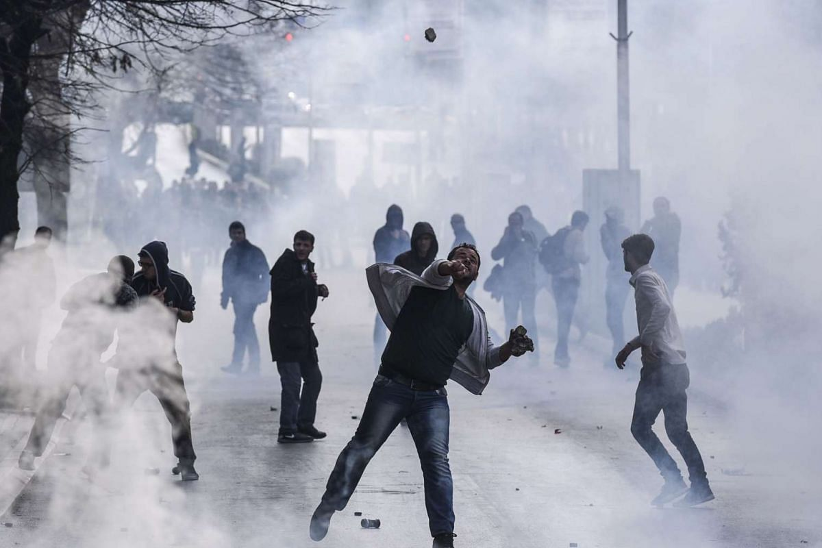 Opposition supporters throwing stones as they clash with riot police in Pristina on Nov 18, 2015, in the latest eruption of a long-running protest against agreements made with Serbia.  PHOTO: AFP