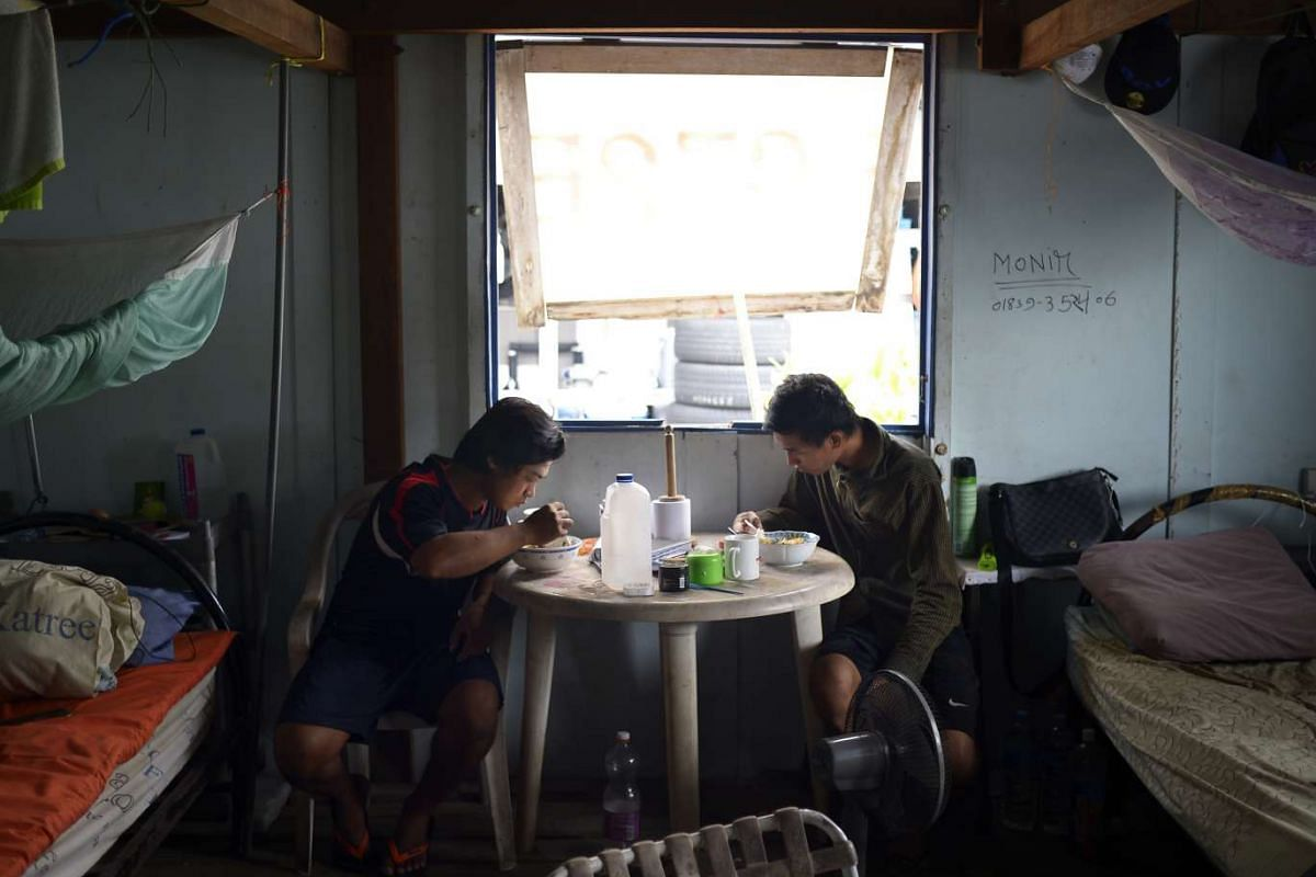 Workers Si Thu Soe Niang (far left), 24, and Ye Min Tun having lunch in their room on the oyster farm off Pulau Ubin. The duo are from Myanmar and started work on the farm about five months ago after new owners bought it over. The farm owners provide them