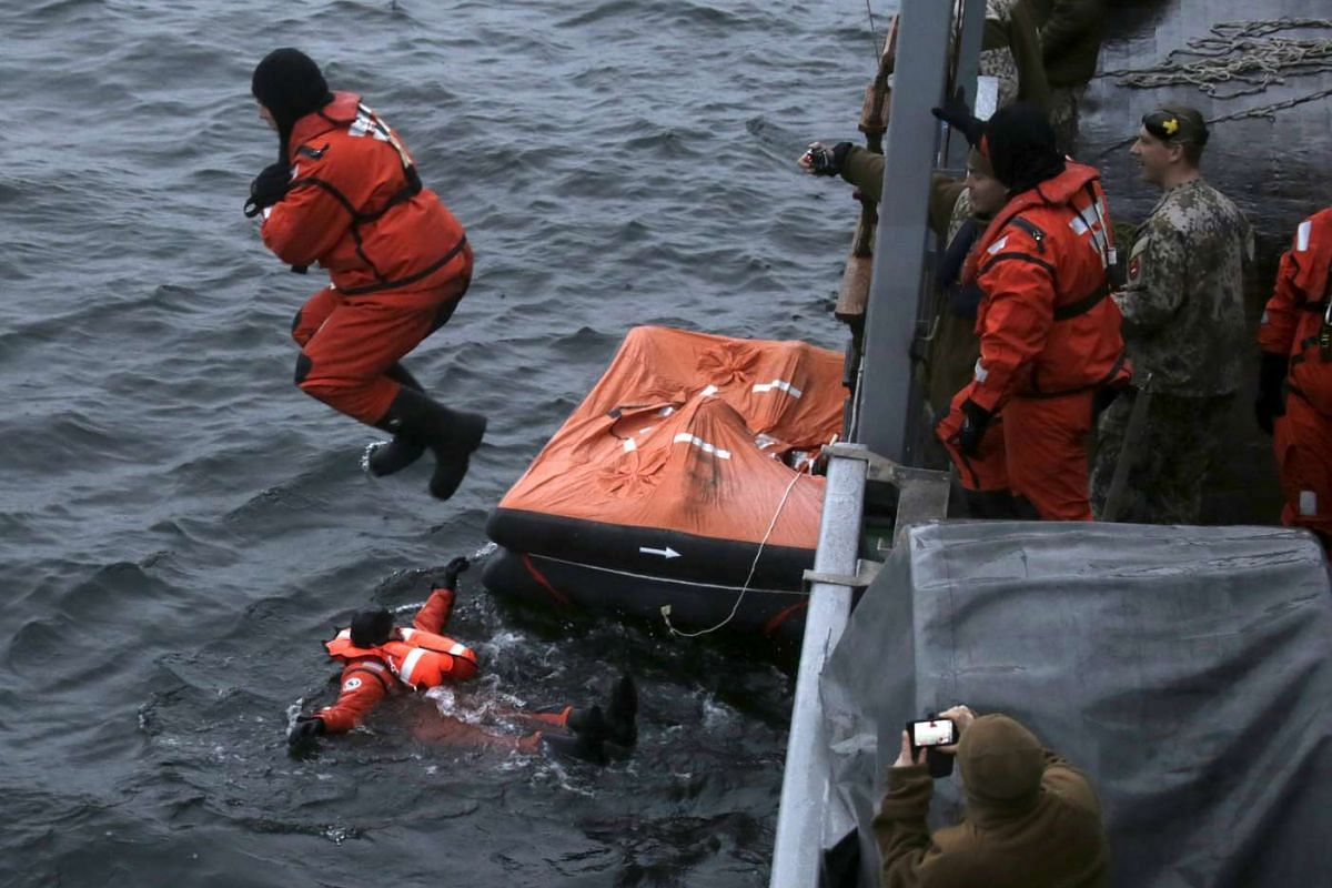 Latvian Navy personnel jump into the sea to simulate a ship capsizing, during a search and rescue exercise in the Baltic sea near Engure, Latvia, Nov 19, 2015.