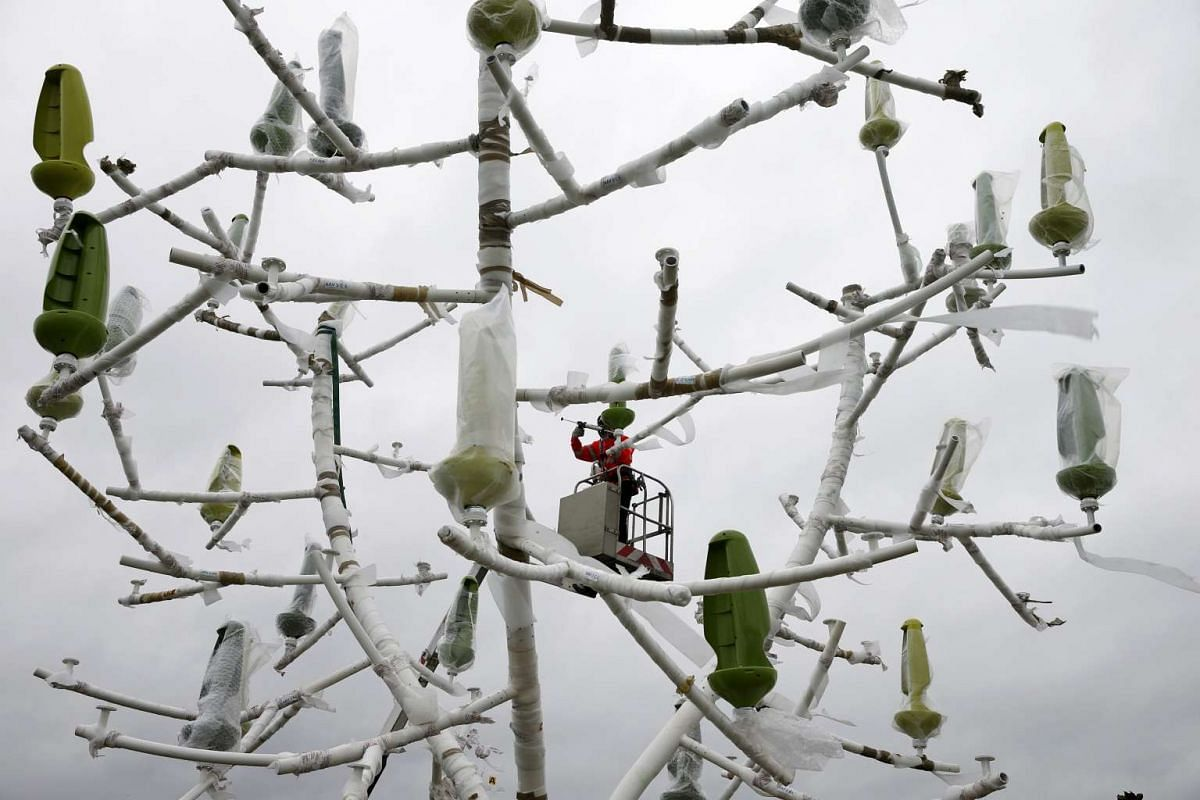 Men work on the site where the upcoming COP21 World Climate Summit will be held at Le Bourget, near Paris, France, Nov 19, 2015.