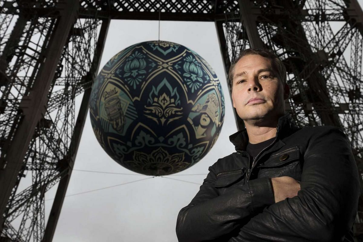 """US artist Shepard Fairey poses with his """"Earth Crisis"""" globe displayed on the Eiffel tower in Paris on Nov 20, 2015 as part of the organisation of the Conference on Climate Change COP21-CMP11, also named """"Paris 2015""""."""