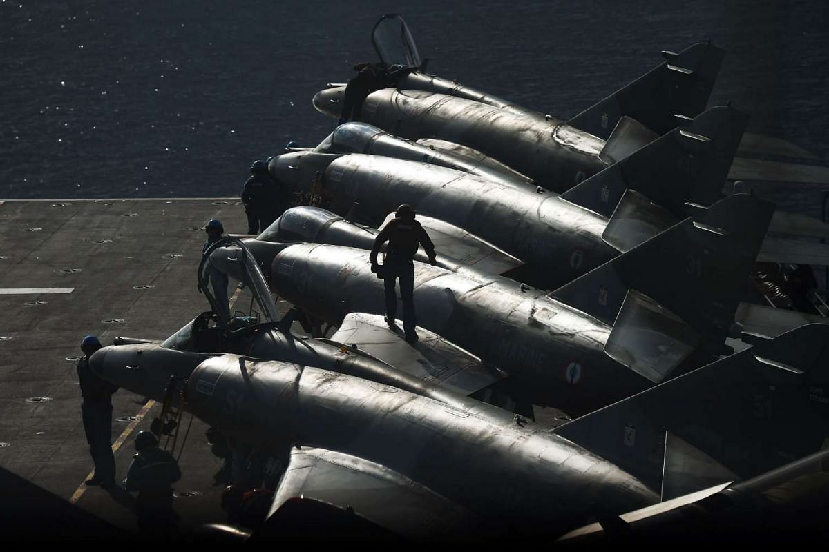 French navy soldiers work on Super Etendard jet fighters on the flight deck of the French Charles-de-Gaulle aircraft carrier on Nov 22, 2015 in the eastern Mediterranean Sea.