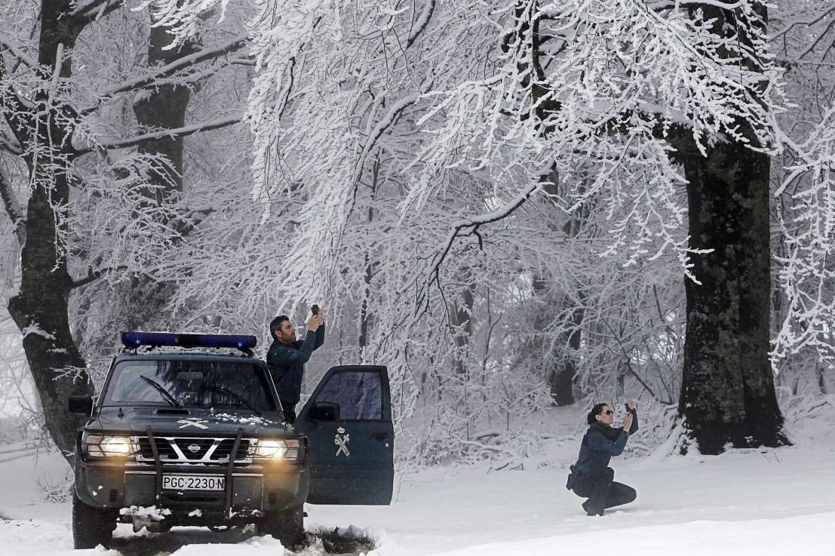 Two Spanish Civil Guard officers take photos in a snow-covered forest in Mezquiriz, Navarra, northern Spain, on Nov 22, 2015.