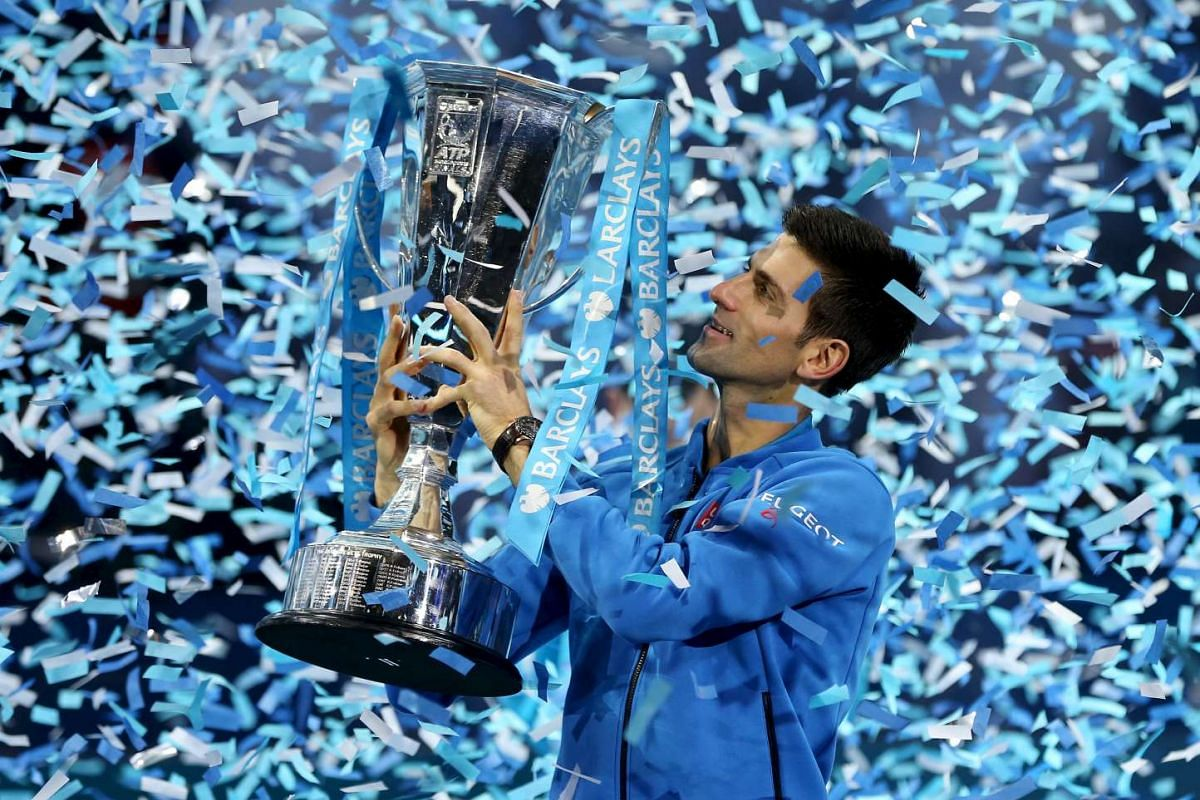 Serbia's Novak Djokovic celebrates with the trophy after winning the Barclays ATP World Tour Finals against Switzerland's Roger Federer, on Nov 22, 2015.
