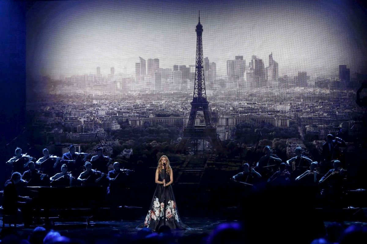 """Celine Dion performs """"Hymne a l'amour"""" (Ode to love) in honor of the victims of the recent Paris attacks as an image of the Eiffel Tower is shown in the background during the 2015 American Music Awards in Los Angeles, California on Nov 22, 2015"""