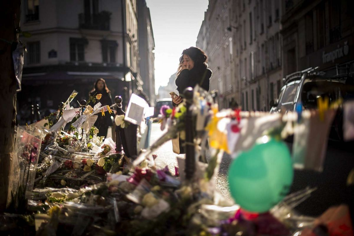 A woman cries as she stands at a makeshift memorial for a tribute to the victims of a series of deadly attacks in Paris, in front of the Casa Nostra restaurant in Paris on Nov 23, 2015.