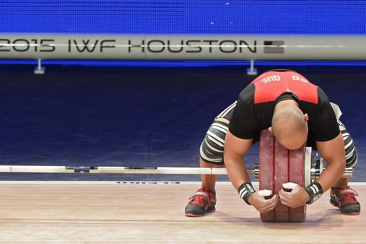 Bredni Mendoza Roque of Mexico hugging the weight after completing a lift in the Clean and Jerk at the George R. Brown Convention Center in Houston, Texas, on Nov 23, 2015.