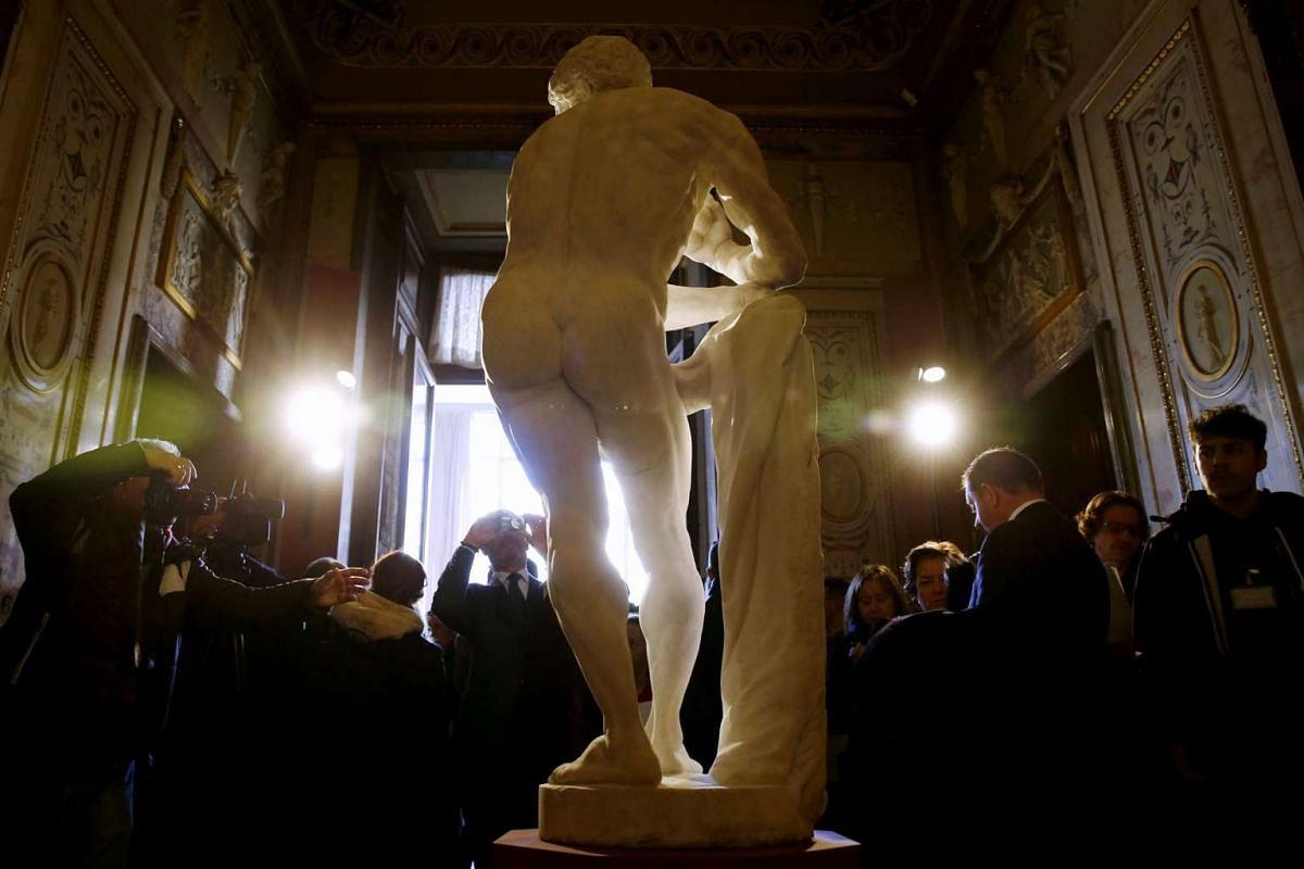 Visitors photograph a marble statue of Hercules, sculpted on the 17th century by an anonymous Genoese artist, Nov 24, 2015.
