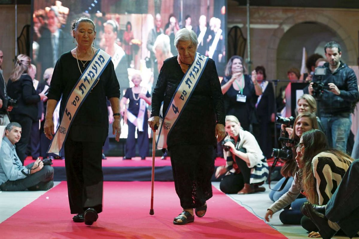 Judith Rosenzweig (Right), 81, and Rivka Shtanger, 74, both Holocaust survivors, walk on a runway during a beauty contest for survivors of the Nazi genocide in the northern Israeli city of Haifa, on Nov 24, 2015.