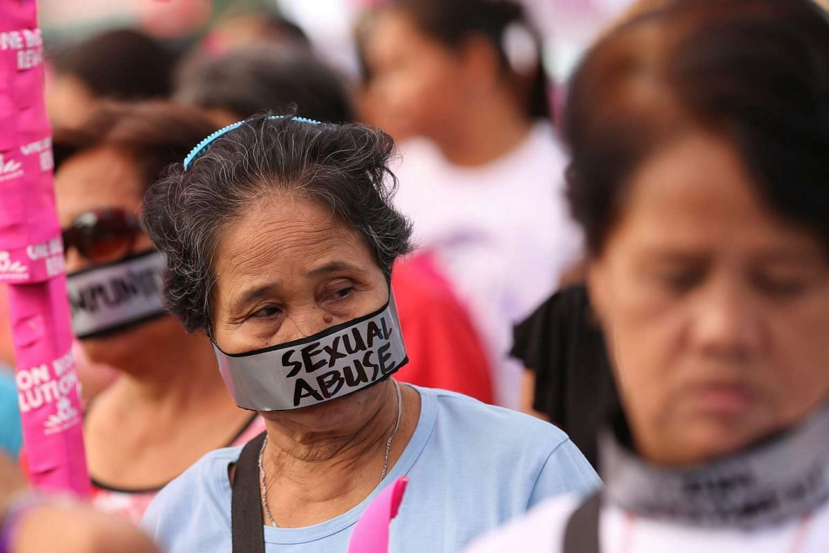 Filipino women activists with duct tape covering thier mouth reading 'Sexual Abuse' take part in a caravan marking the International Day for the Elimination of Violence against Women in Manila, Philippines, on Nov 25, 2015.