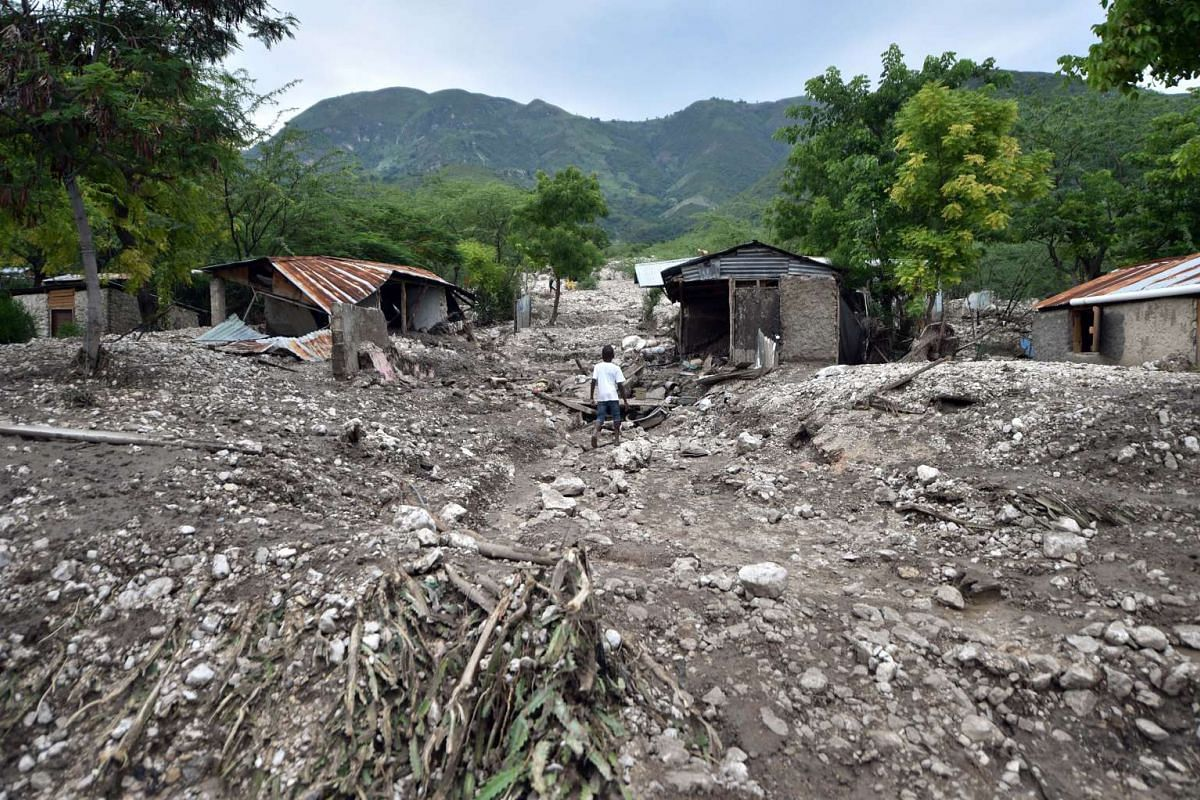 A picture taken on Aug 29, 2015 shows a boy walking past houses destroyed by a mudslide caused by the rains from tropical storm Erika in Montrouis, Haiti. Weather-related disasters have grown more frequent over the last 20 years, claiming more than 6