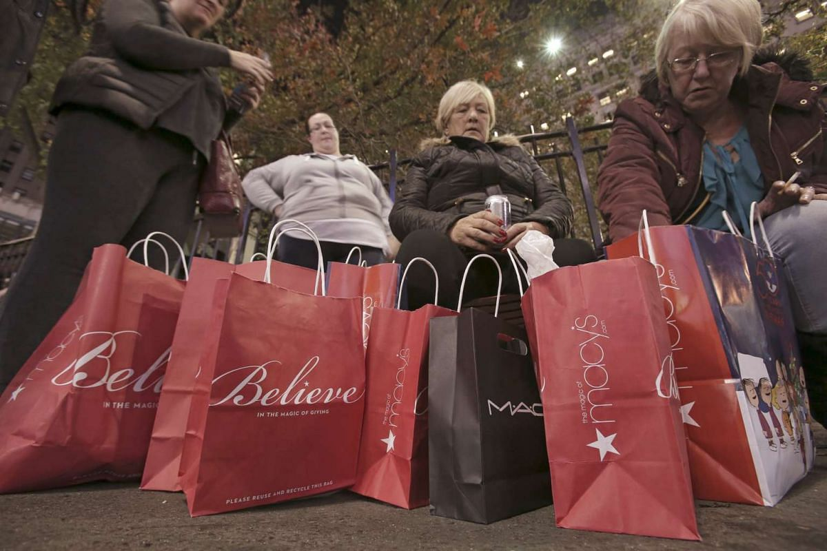 Women sitting outside Macy's Herald Square store after shopping during the early opening of the Black Friday sales on Nov 26, 2015.