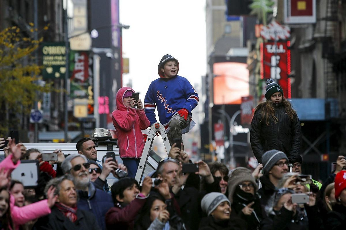 A child watches the parade from a ladder.