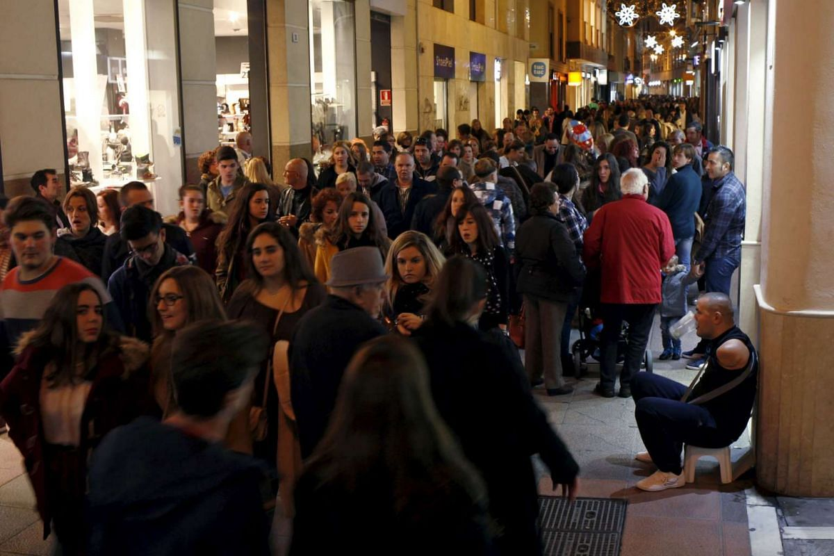 Shoppers along a shopping street in downtown Malaga, southern Spain on Nov 27, 2015.