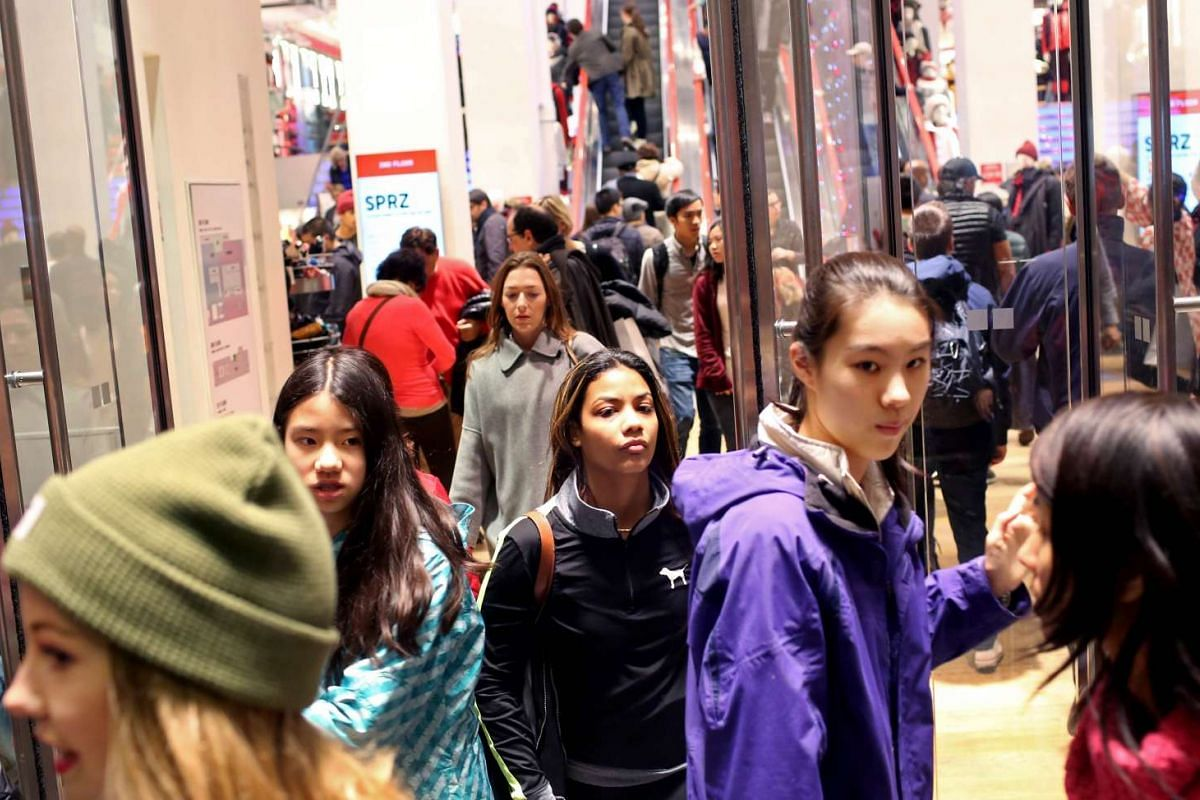 Shoppers walking out of Uniqlo on 666 5th Avenue in New York City on Black Friday.