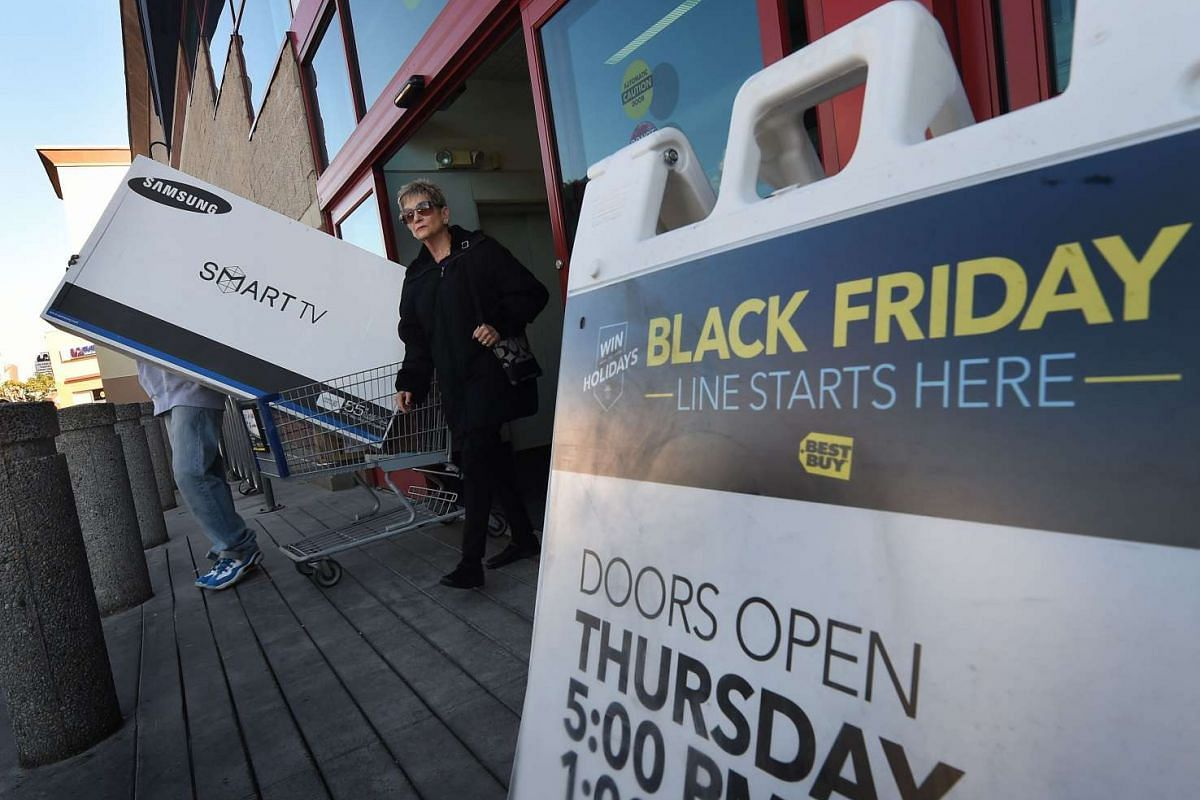 Shoppers leaving a Best Buy store with a television during a Black Friday sale in Los Angeles, California on Nov 27, 2015.