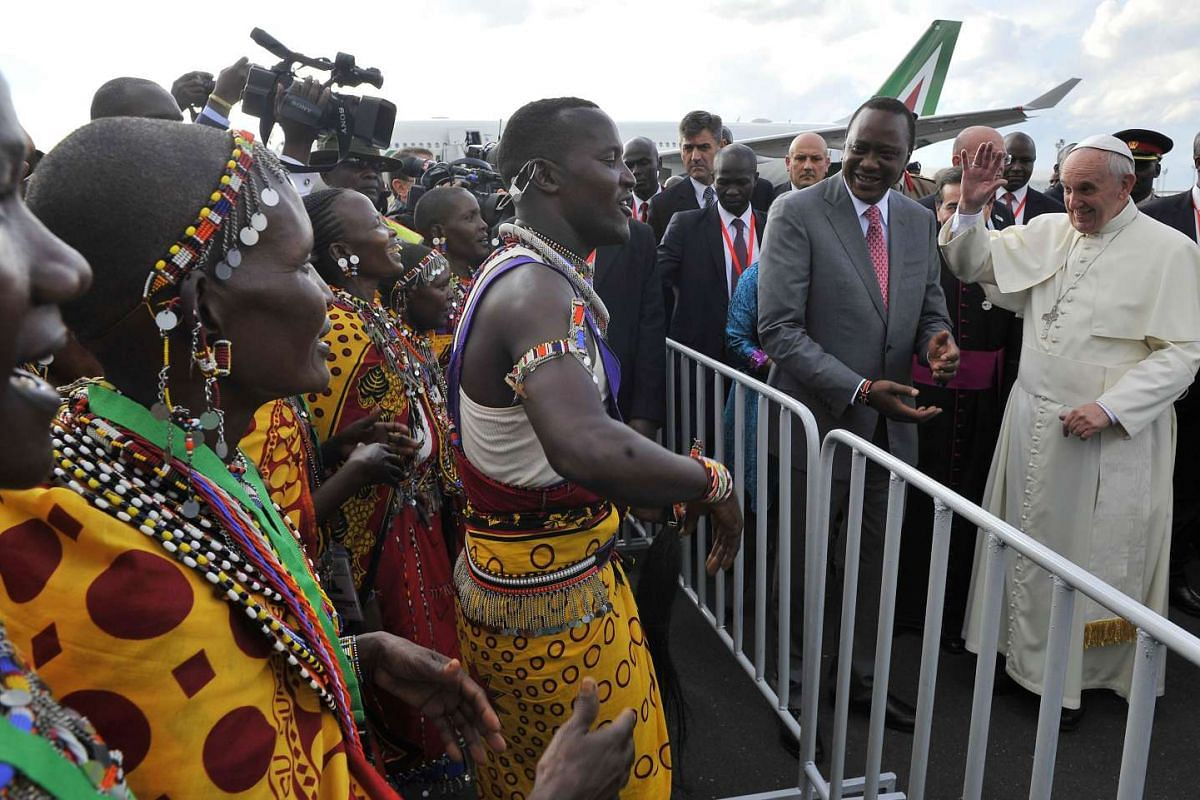 Pope Francis (right) flanked by Kenya's President Uhuru Kenyatta, is entertained by Maasai traditional dancers after arriving in Nairobi on Nov 25, 2015.