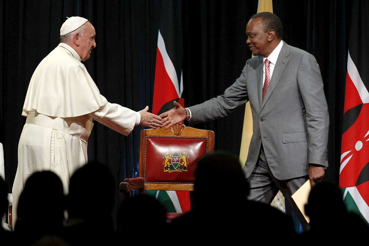 Pope Francis (left) greeting Kenya's President Uhuru Kenyatta after delivering a speech during a reception at the State House in Nairobi on Nov 25, 2015.