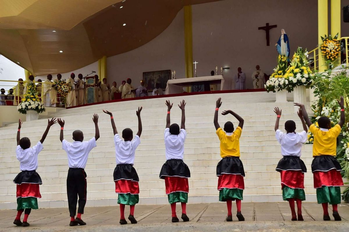 Children gesturing as Pope Francis celebrates a giant open-air mass at the University of Nairobi on Nov 26, 2015.