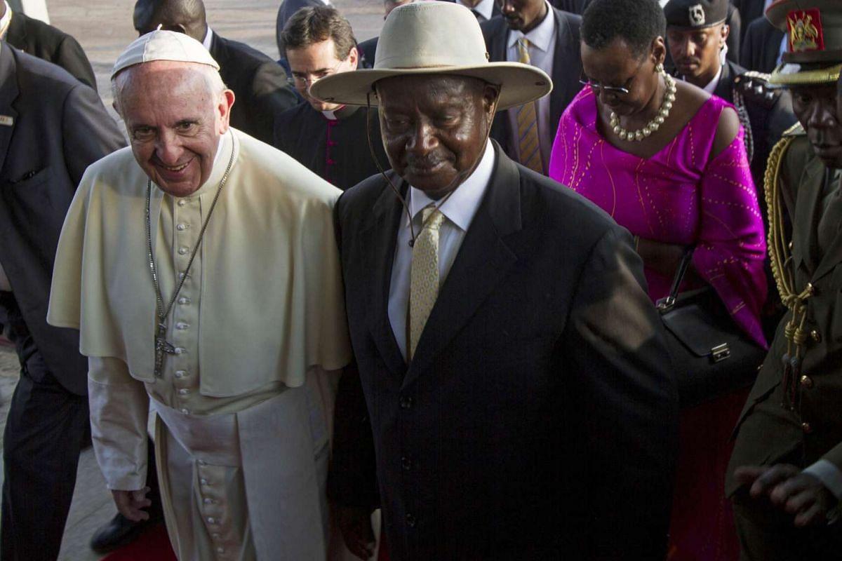 Pope Francis (left) walking along Uganda's President Yoweri Museveni upon his arrival in Entebbe on Nov 27, 2015.