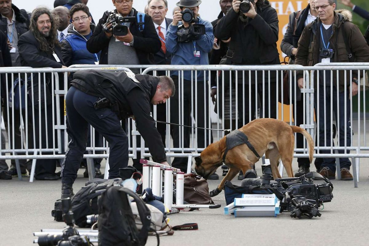 A French policeman with a sniffer dog inspects journalists' equipment as tight security continues on the opening day of the World Climate Change Conference 2015 (COP21) at Le Bourget, near Paris, France, Nov 30, 2015.