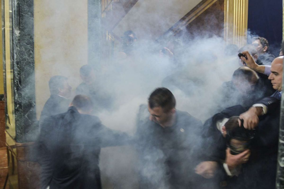 Members of the Parliament leave the hemicycle after tear gas was launched by opposition lawmakers, at the Kosovo's parliament in Pristina, on Nov 30, 2015.