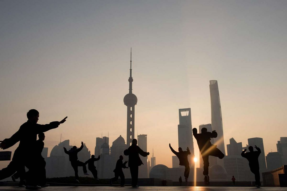 Men doing their morning exercises in front of the skyline of the Lujiazui Financial District in Pudong in Shanghai on Dec 1, 2015.