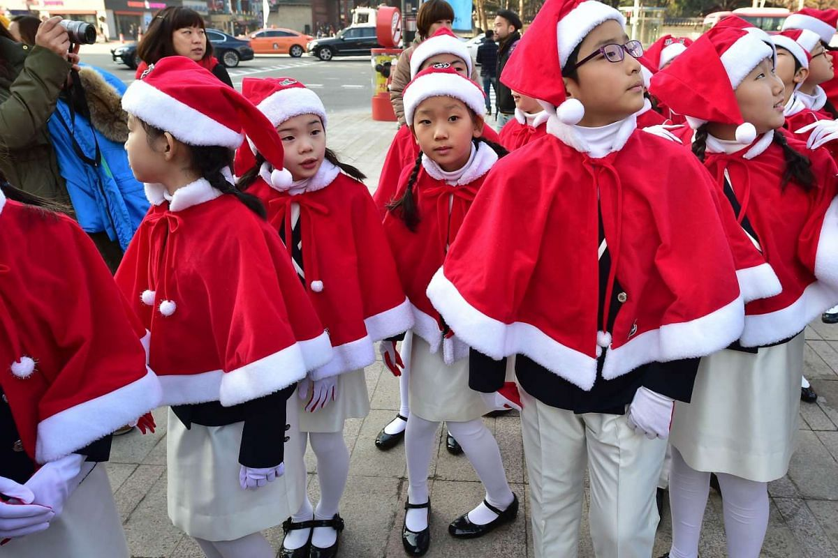 Children wearing Santa Claus outfits stand in a line before the launch of Salvation Army's year-end fundraising campaign at Seoul plaza in Seoul on Dec 1, 2015.