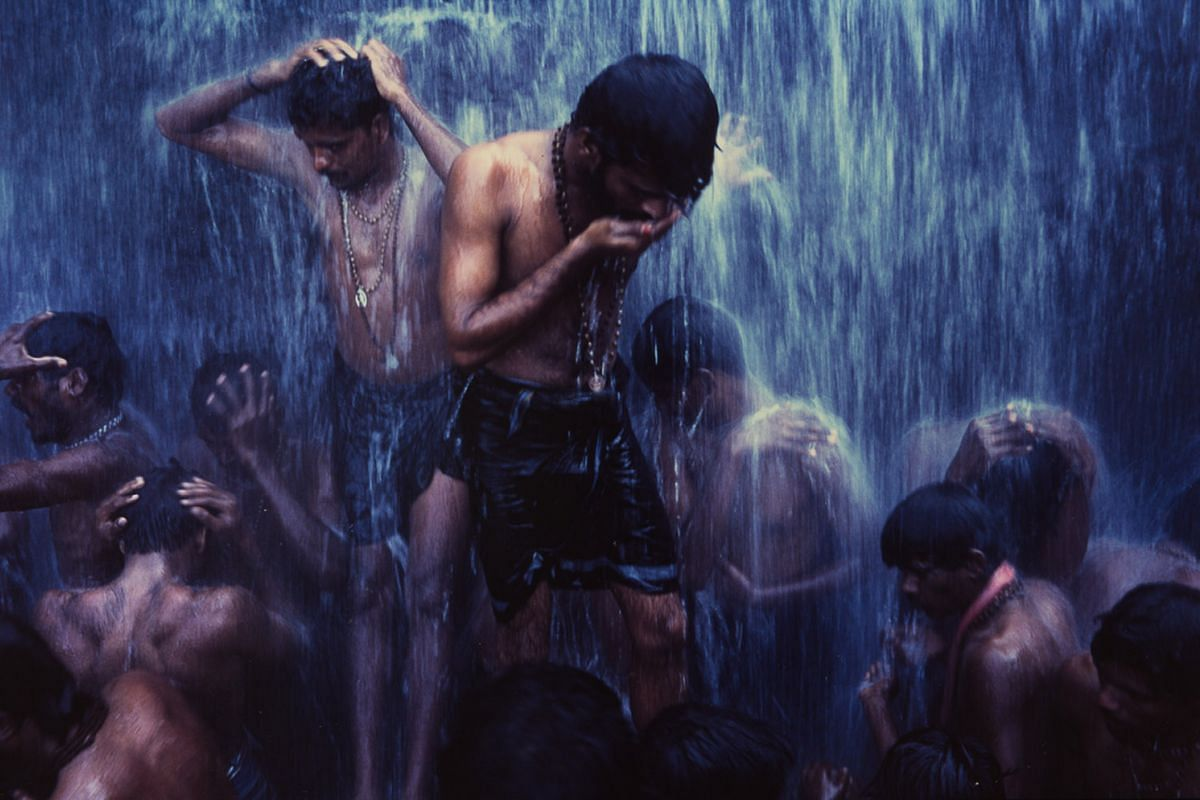 Shiva devotees ritually bathe under a waterfall at Coutralam, Tamil Nadu, India, 1996.