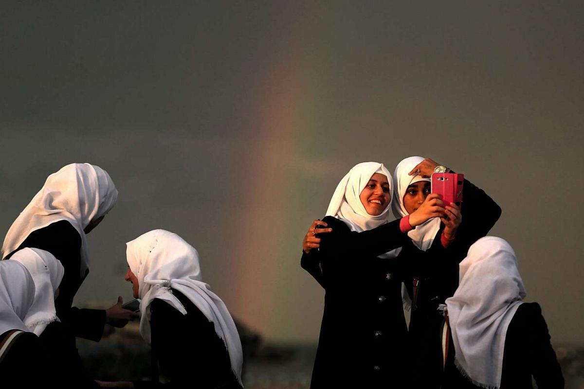 Palestinian students posing in front of a rainbow over Gaza City after a storm on Dec 1, 2015.