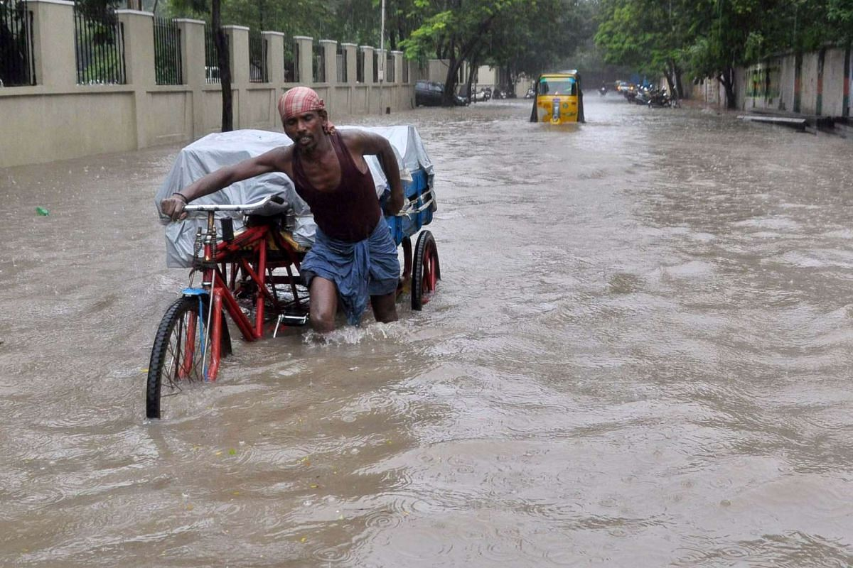 An Indian labourer pushing his trishaw through floodwaters in Chennai on Dec 1, 2015.