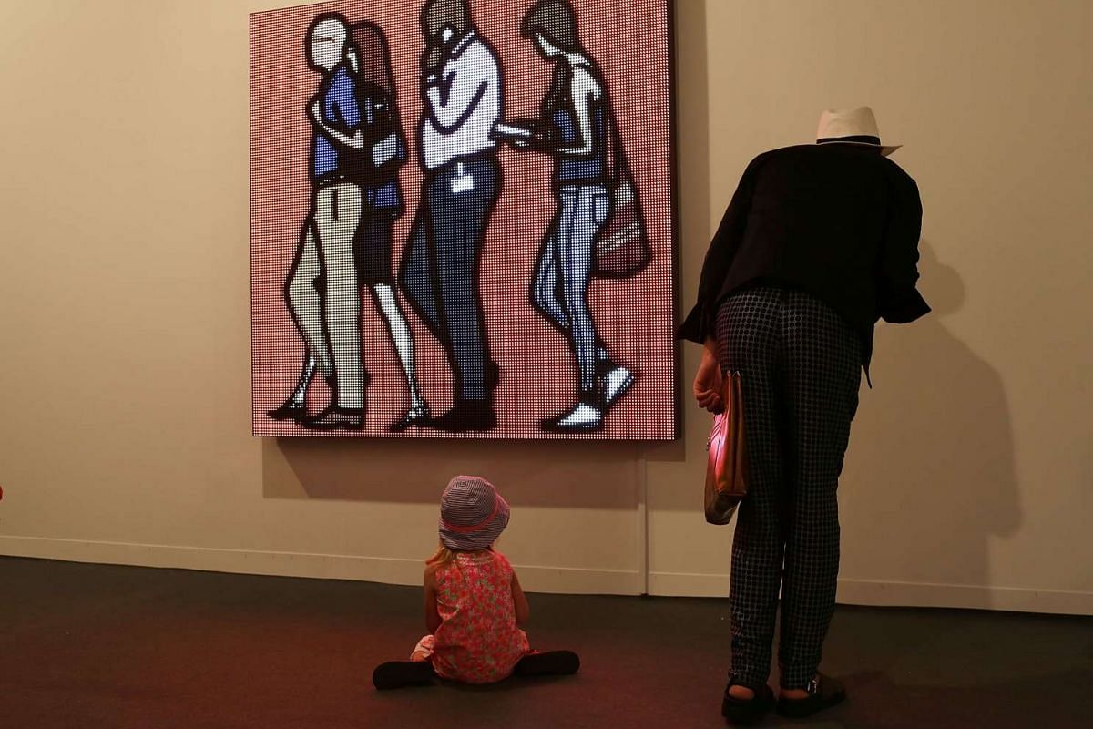 """People look on at a piece by artist Julian Opie titled, """"People"""", on display during the opening day of Art Basel on Dec 2, 2015 in Miami Beach, Florida."""