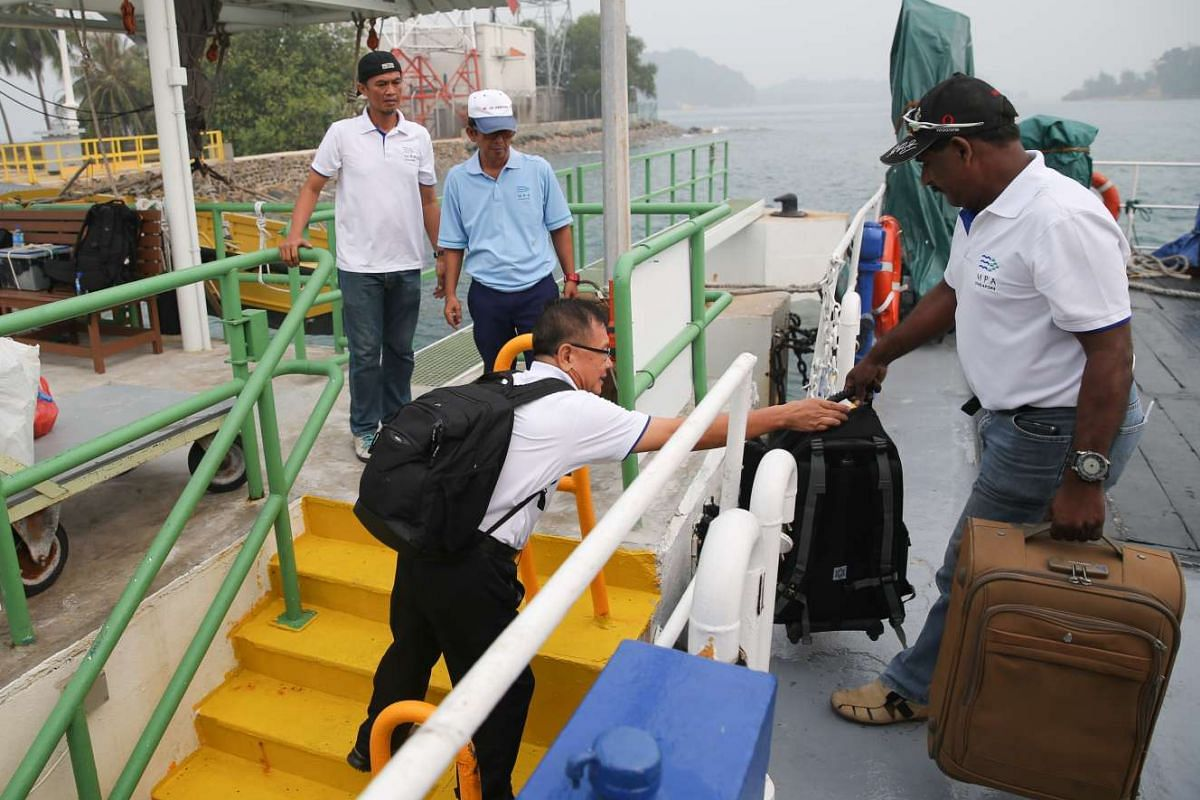 Mr Uthrapathi and Mr Lee Kwang Liang (with backpack) arrive at Raffles Lighthouse by ferry to relieve their colleagues and start their shift.