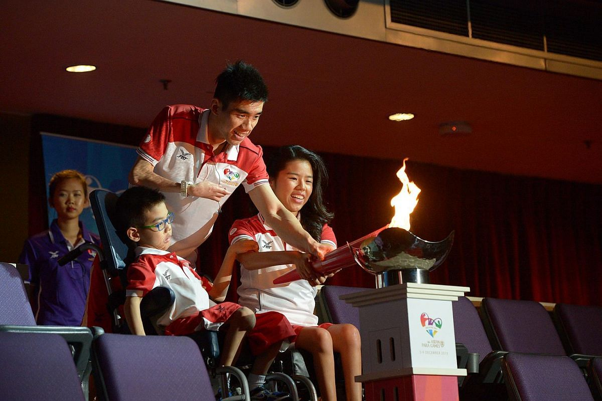 (From far right) Swimmer Yip Pin Xiu joined hands with badminton player Tay Wei Ming and nine-year-old boccia player Aloysius Gan to light the cauldron.
